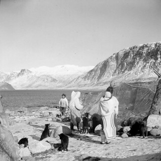 A group of Inuit standing outside near their tupiit (tents), showing Pangnirtung Fiord and Mount Duval in the background... / Un groupe d'Inuits debout, dehors, près de leurs tentes, en arrière-plan le fjord Pangnirtung et le mont Duval...