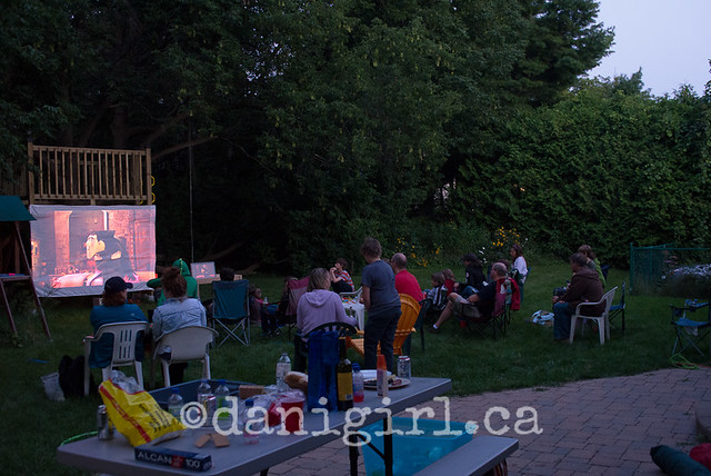 outdoor photo of families watching a movie in backyard