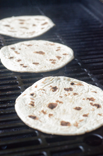 Flatbread being toasted on a grill.