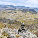 Cairn along hiking trail from mountaintop into valley