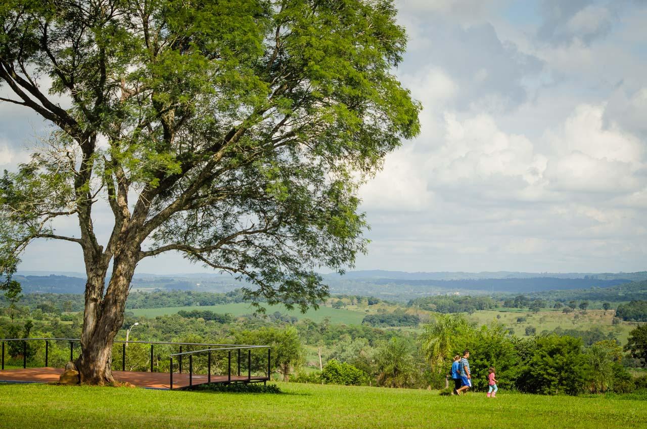 Una familia camina por los campos verdes de la Misión Jesuítica de Jesús de Tavarangué, sitio donde los visitantes pueden disfrutar del paisaje desde los distintos miradores. (Elton Núñez).