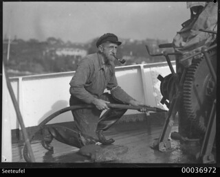 Boatswain Karl Muller smoking a pipe and hosing the deck of SEETEUFEL
