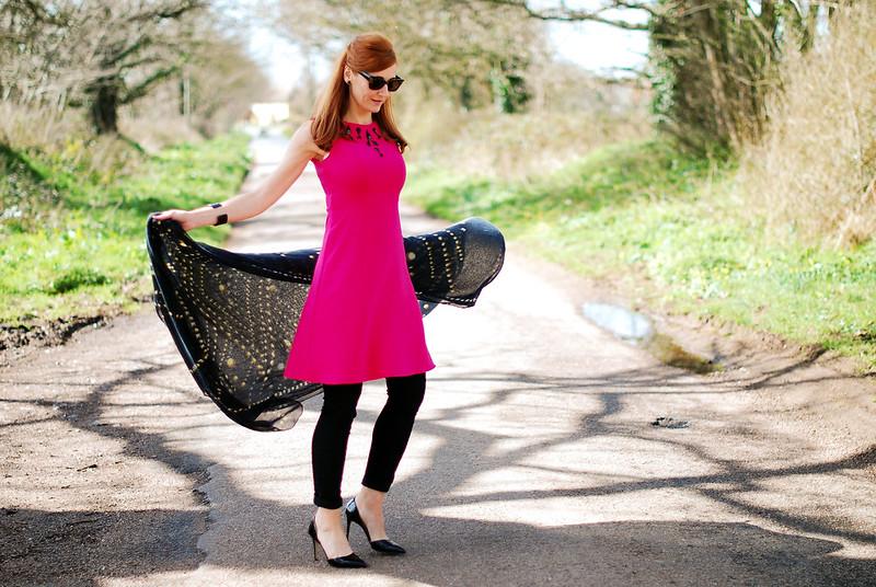 Pink embellished dress over black pants