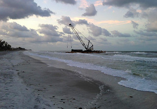 A 140-foot barge is shown beached on Long Boat Key, Fla., Wednesday, April 9, 2014. Due to weather conditions, the barge spuds were unable to hold the barge in position and it began drifting until it ran aground on the beach at Long Boat Key. (U.S. Coast Guard photo)