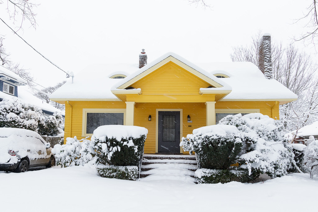 A cheery yellow house in the snow