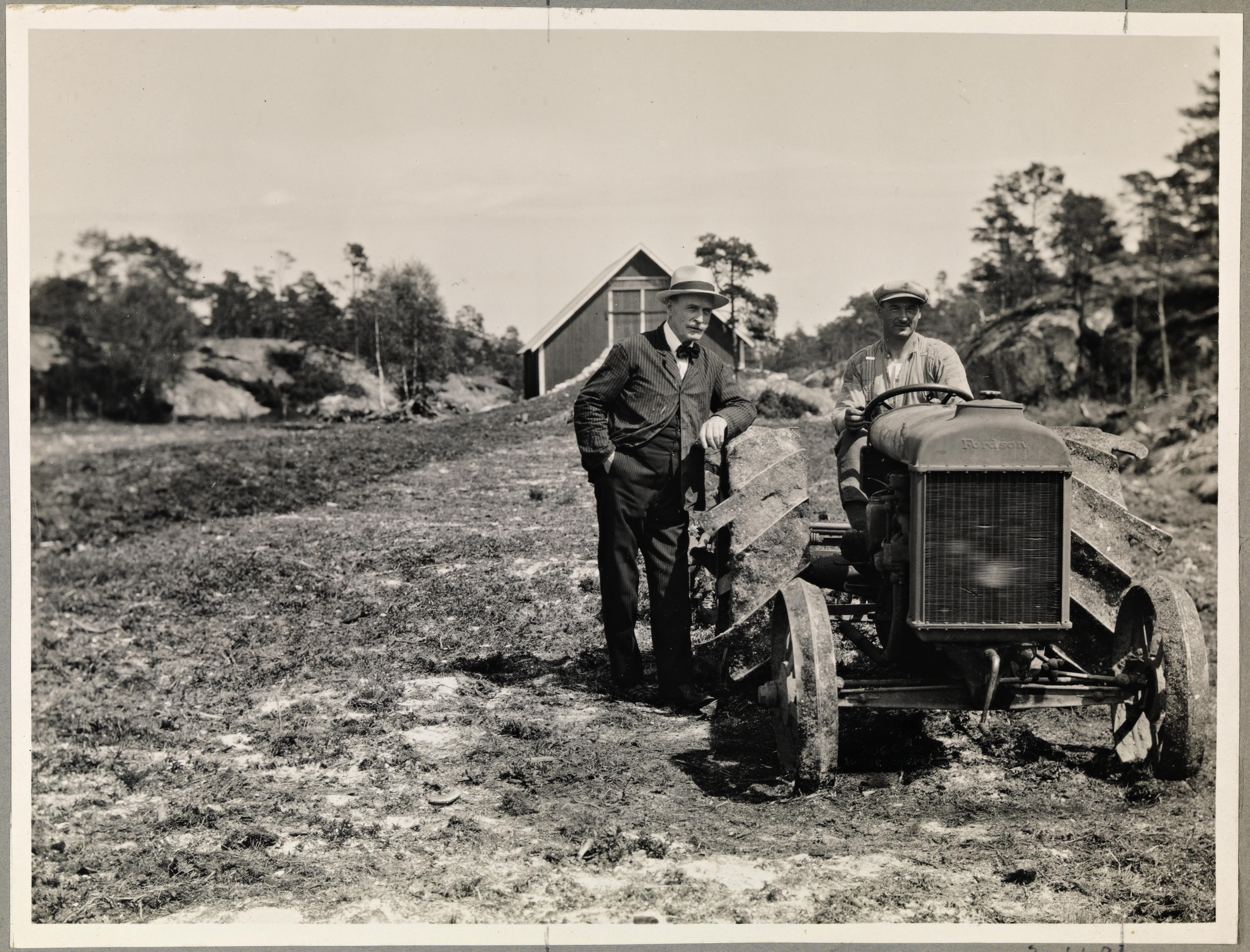 Knut Hamsun (1859-1952) ved siden av en uidentifisert mann på traktor, juni 1929