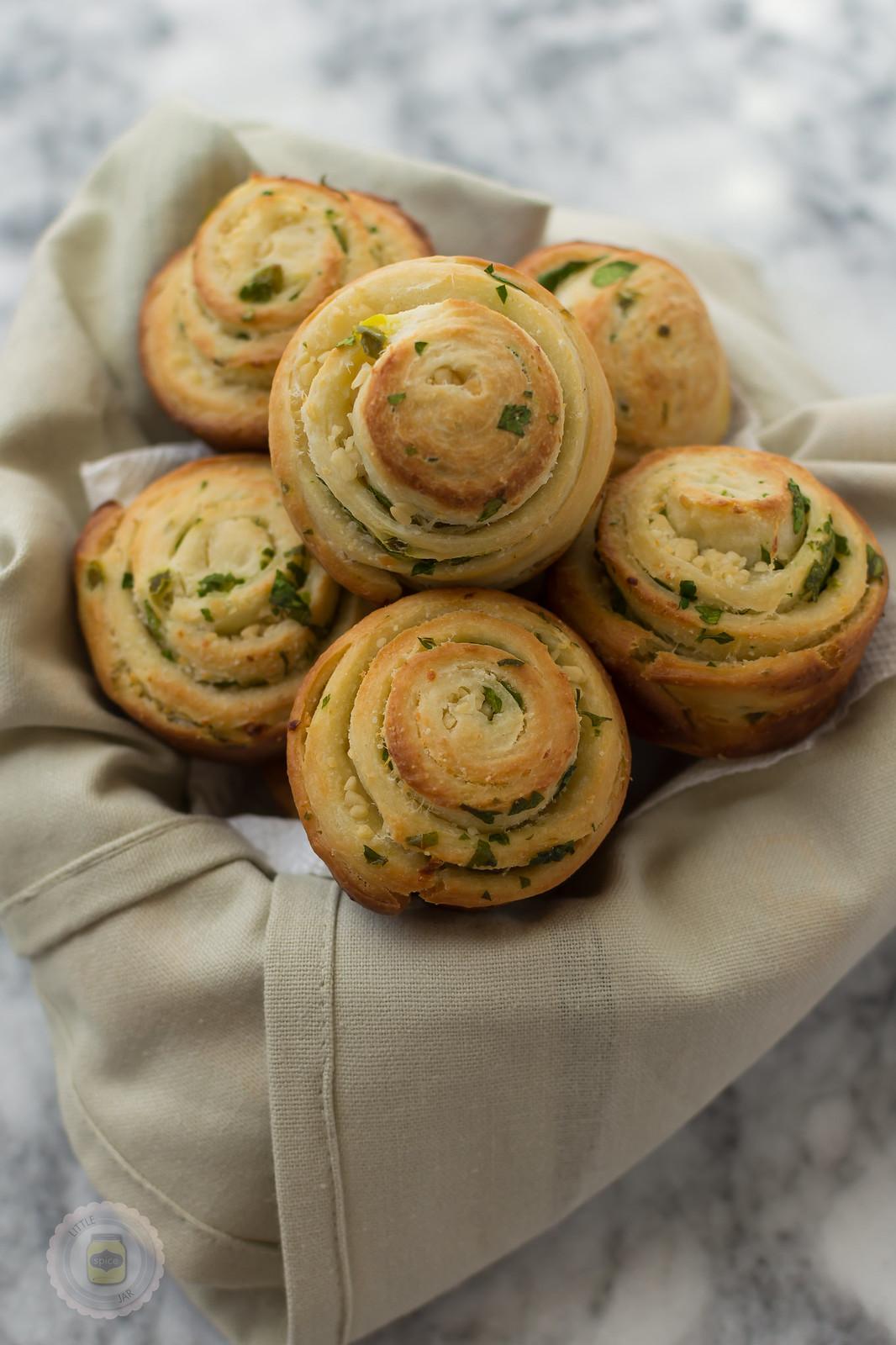 jalapeno parmesan swirl bread rolls in towel lined basket showcasing swirls