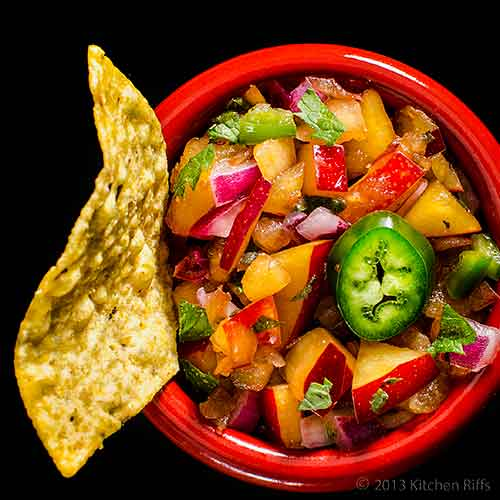 Plum Salsa with tortilla chip in red ramekin, overhead view on black
