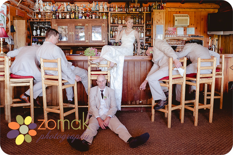 Hilarious shot of the bride and groomsmen as they sit at the bar at their wedding reception in Seeley Lake.
