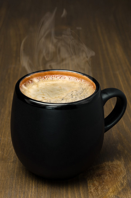 black mug of coffee with foam on a wooden table