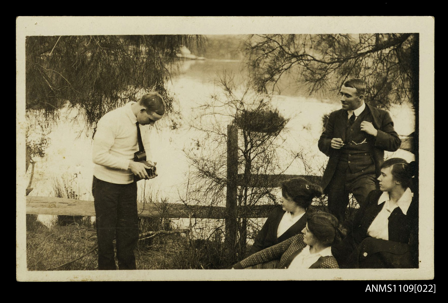 Photographic portrait postcard of a young man taking a photograph of a group