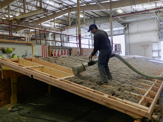 Blazer worker fills a classroom roof with insulation.