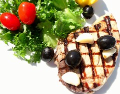 GRILLED TUNA STEAK, GARLIC CONFIT WITH BLACK OLIVES AND GREENS IN RASPBERRY VINAIGRETTE