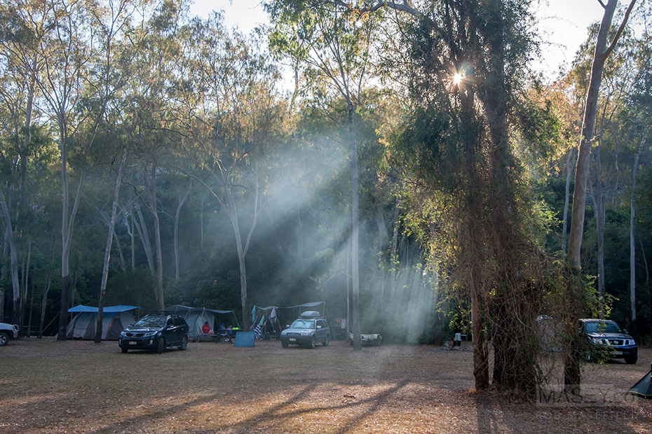 Sun streams through the smoke remaining from last night's camp fires.