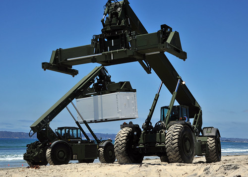wo Kalmar rough terrain container handlers work in tandem to move supplies off an improved Navy lighterage system