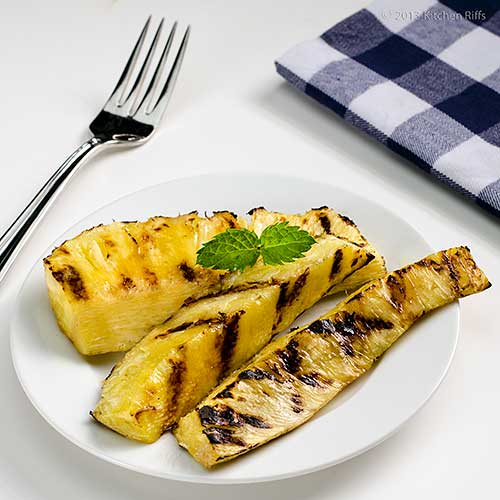 Grilled Pineapple wedges on plate with mint garnish