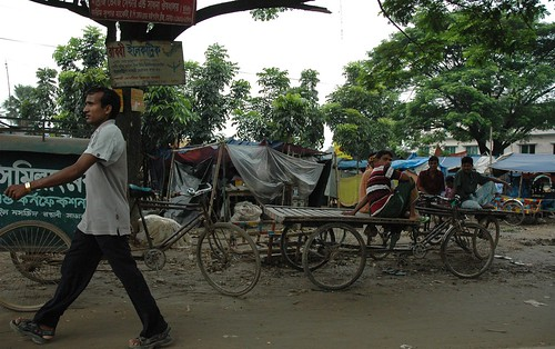 Man out for a stride, rickshaw drivers, carts, men taking a break, plastic tent, rickshaw capital of the world, dirt road, trees, Dhania, Dhaka, Bangladesh by Wonderlane