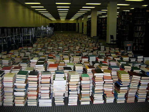 Image of stacked books covering entire floor of library
