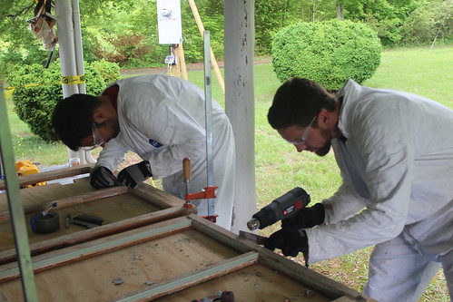 Military veteran Tyler Price, left, of the Student Conservation Association, and Josh Carr of Historicorps scrape lead paint off of historic window sashes of a Thornburg Farm historic building during a restoration project on the Uwharrie National Forest. (Photo courtesy Michael Salisbury)