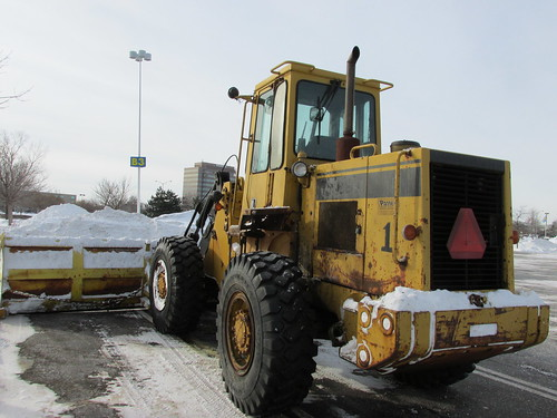 A front end loader tractor equipped with an extra wide snowplow attatchment.  Schaumburg Illinois.  Wednsday, January 8th, 2014. by Eddie from Chicago