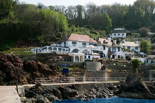 The white-washed buildins of the Cary Arms tucked into the cliffside