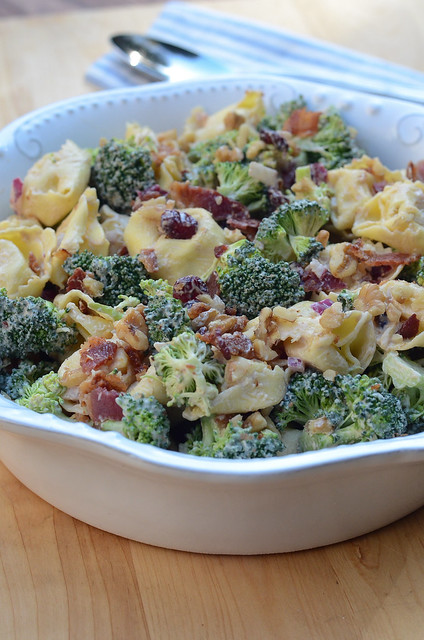 A bowl of tortellini with broccoli and bacon.