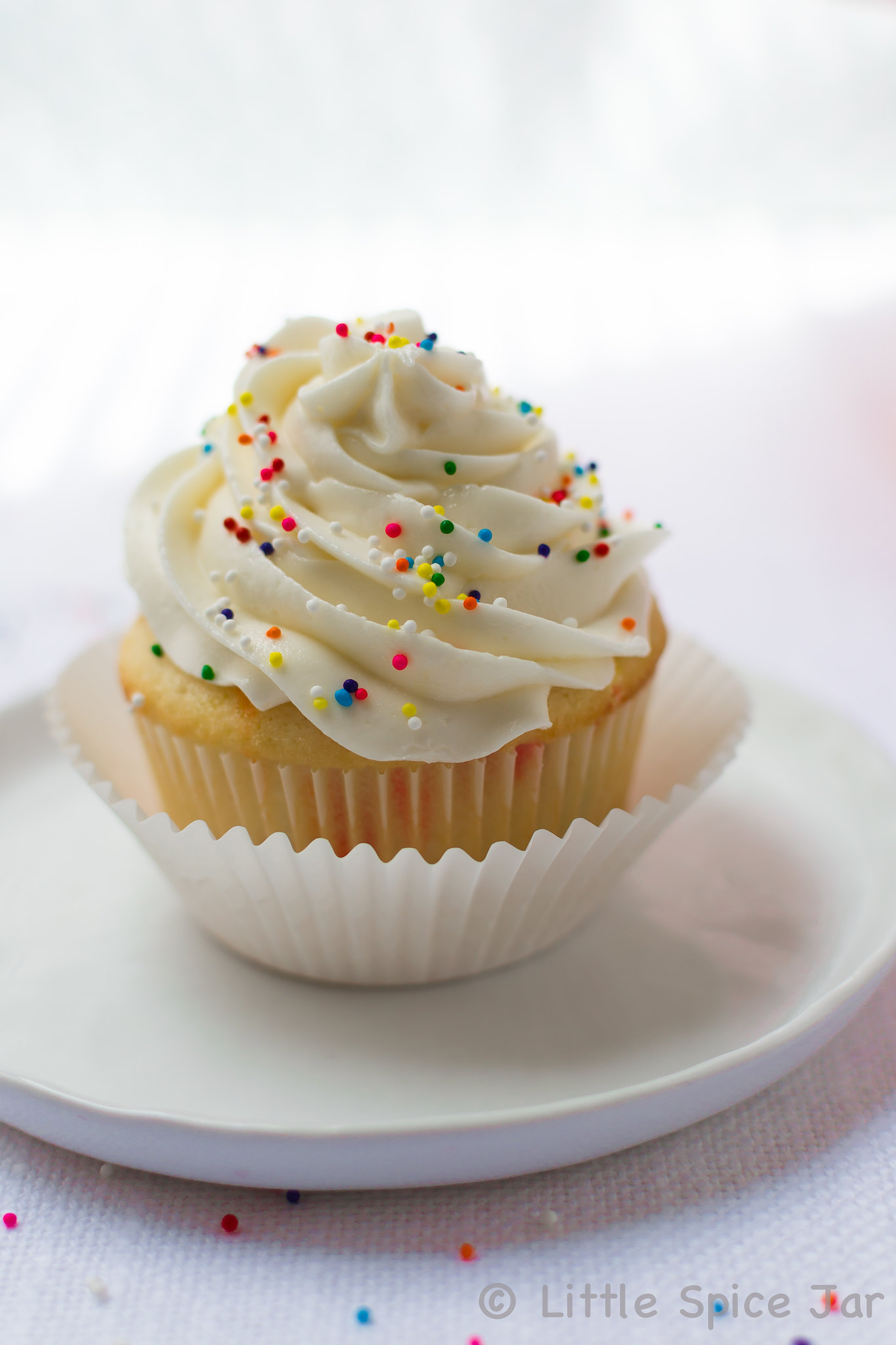 prepared funfetti cupcake with whipped topping and sprinkles on white plate on white surface