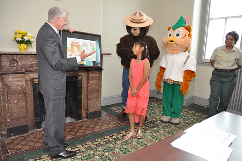 U.S. Forest Service Chief Tom Tidwell talks about a drawing by Joyce Qin, the 11-year-old Memphis-area girl who became the 2014 Smokey Bear & Woodsy Owl Poster Contest winner. Looking on from left to right is Smokey Bear, Woodsy Owl and Renee Green-Smith, National Information Center manager. (U.S. Forest Service/Dominic Cumberland)