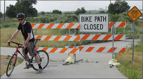 Photo of cyclist turning around at closed trail barricade