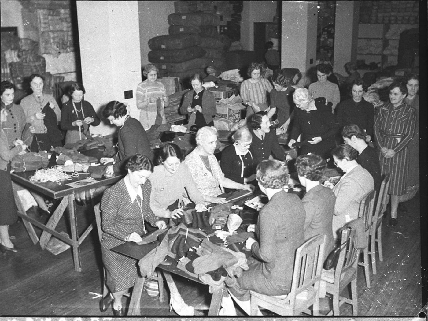 Women volunteer workers doing up clothing parcels at the ACF rooms (taken for Australian Comforts Fund), by Sam Hood, c. 1944