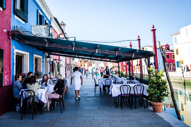 Diners relax on the canalside patio of one of Burano's most popular restaurants, Il Gato Nero.