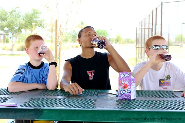 Three boys drinking Kool aid beverage in the shade.