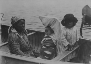 Cree woman, young girl, and an infant in a cradle board in a canoe / Une femme crie, une jeune fille et un enfant dans un porte-bébé à bord d'un canoë