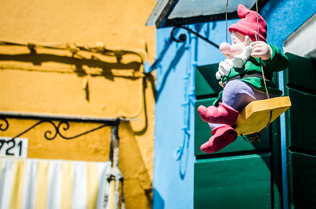 A gnome swings from the windowsill in the middle of Burano, Italy.