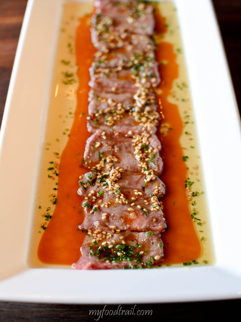Wagyu new style - thin slices of wagyu beef, lightly seared with hot oil & finished with ginger, chives & yuzu soy - Sake Restaurant, Melbourne