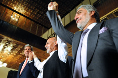 U.S. Secretary of State John Kerry raises hands with Afghan presidential candidates Ashraf Ghani, left, and Abdullah Abdullah, right, at the United Nations Mission Headquarters in Kabul, Afghanistan on July 12, 2014, after they told reporters about the details of an agreement on a technical and political plan the Secretary helped broker to resolve the disputed outcome of the election between them. [State Department photo/ Public Domain]