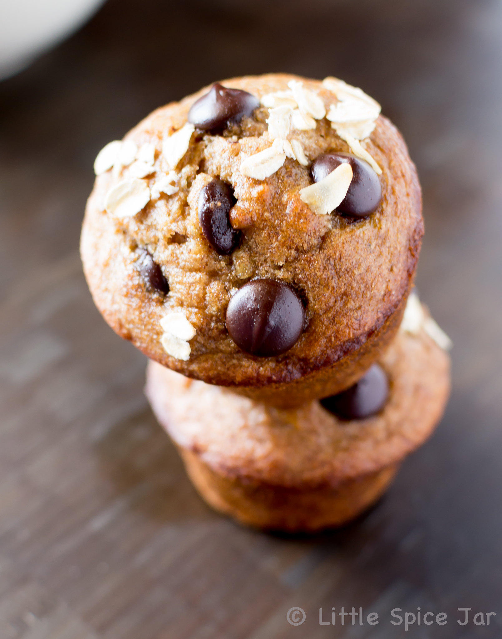 stack of two chocolate chip banana muffins showing oats and chips