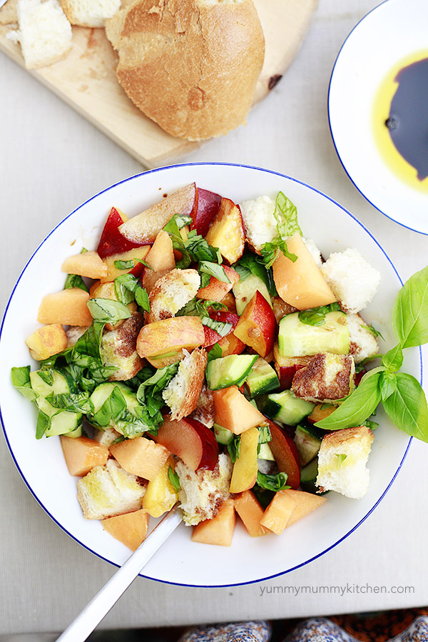 Stone Fruit and Melon Panzanella with fresh basil in a white bowl.
