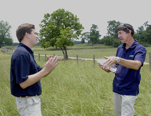 NRCS District Conservationists Mike Liskey talks to Chase Milner with the Shenandoah Valley Battlefields Foundation on optimum grazing and mowing height for grasses in this paddock, which is part of a rotational grazing system installed with NRCS assistance. NRCS photo.