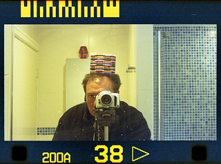 reflected self-portrait with Nikon Pronea-S camera and ersatz lego hat