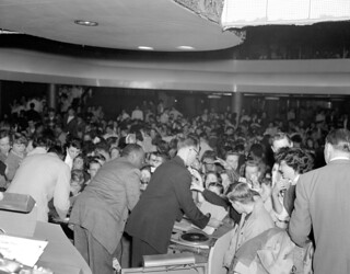 Chuck Berry (left front with back to camera) and another performer sign autographs at the Edmonton Gardens, Alberta
