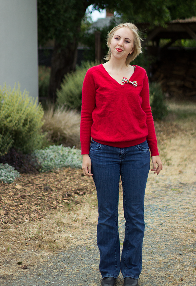 floral bow brooch, bright red cashmere sweater, bootcut blue jeans