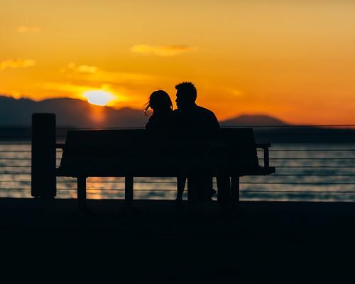 streetphotography seattle couple romantic bench alki westseattle pacificnorthwest canon 4x5 45 orange elliotbay pugetsound water depthoffield dof yellow silhouettes sunset urbandocumentary canon135mmf2lusm canoneos5dmarkiii johnwestrock washington