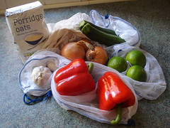 "A selection of vegetables, each in its own white mesh bag.  A cloth shopping bag is just visible at the back of the pile, and a paper bag labelled ""Simple... Porridge Oats"" stands to one side."