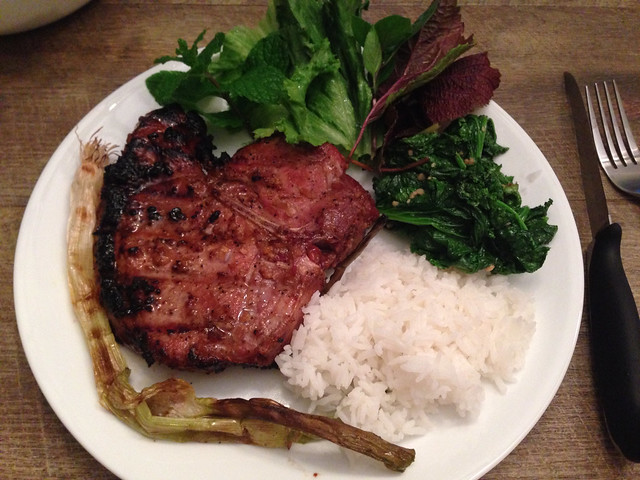 Grilled pork chop with rice, mustard greens, and fresh herbs