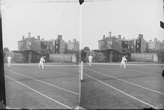 Stereo view of tennis court with a doubles match taking place, large house in the background