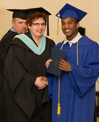 "Marvin Davis, one of two juvenile offenders who earned an associate degree from Barton Community College on Thursday afternoon, accepts an honors-graduate certificate from Barton's Dean of Workforce Training and Community Education Elaine Simmons. ""This will open up some doors for me,"" Davis said, ""despite my rugged past."""