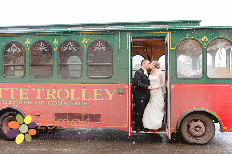 snowy wedding day in butte as bride and groom pose for a portrait on the trolley