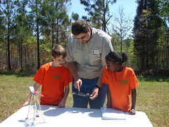 4-H instructor David Self works with 4-H students on a lesson about solar energy and robotics.