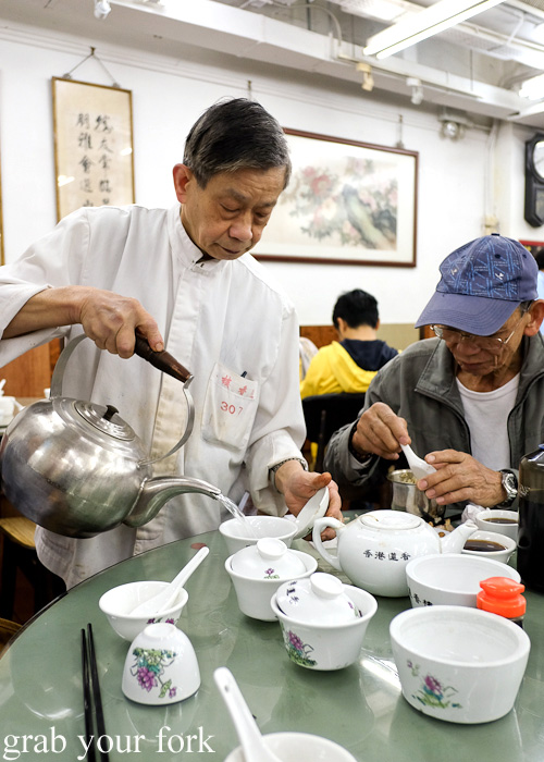 Rinsing tea pots and cups with hot water at Lin Heung Tea House in Central, Hong Kong